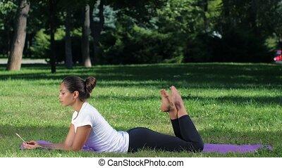 Girl makes a selfie doing yoga. Sunny day in park - Girl...