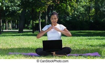 Woman working with laptop sitting lotus pose, woman yoga in...