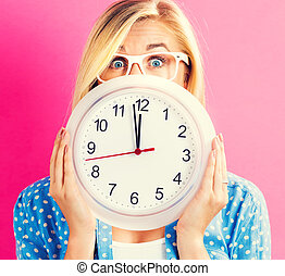 Woman holding clock showing nearly 12 - Young woman holding...