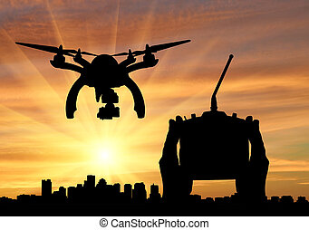 Silhouette flying reconnaissance drone over city and hand...