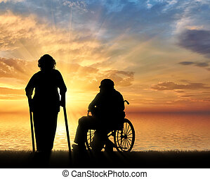 Silhouette of an old woman on crutches and elderly man in a...