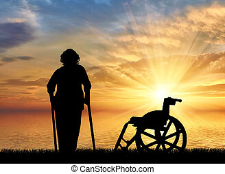 Silhouette of an old woman on crutches on a background of...