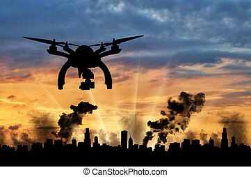 Silhouette flying reconnaissance drone over the city in...