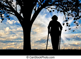 Silhouette of an old woman on crutches resting under a tree....