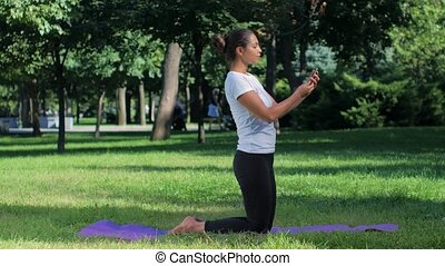 Girl sitting on a mat and doing selfie with smart phone in...
