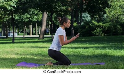 Girl doing selfie with smart phone in the yoga position,...