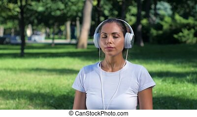 Girl doing yoga in the park and listening music on...