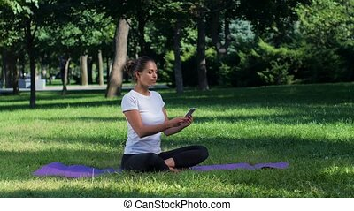 Girl doing yoga in the park and talking on smartphone, girl...