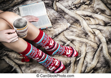 female legs in Christmas socks with a book and  cup of coffee