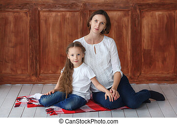 Little girl and her pregnant mom sitting in studio