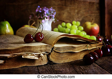 book on wooden background and cherry berry - retro book on...
