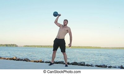 Sportsman picks up a dumbbell with one hand. Slow motion -...