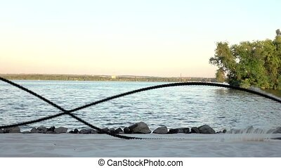 Sportsman battle ropes on the banks of the river. Slow...