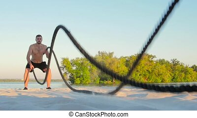 Battle ropes on the banks of the river. Slow motion - Battle...