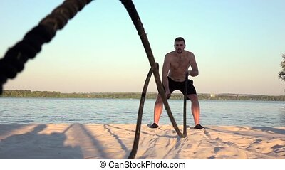 Man conducts training with the ropes on the sandy shore....