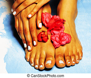 african Female feet and hand, blue pedicure with pink flower...