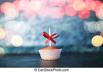 birthday cupcake with a candle bokeh