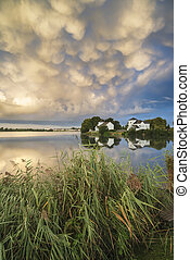 Beautiful mammatus clouds formation over lake landscape...