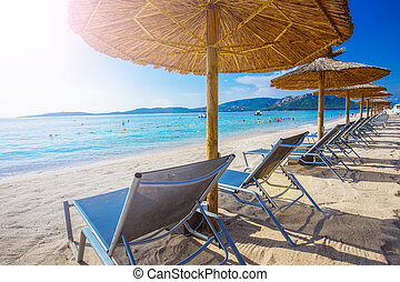 Beach chairs in Corsica, France - Beach chairs with a white...