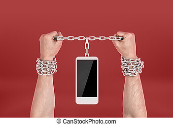 Human hands chained to the phone. Dependence on information...