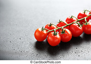 Cherry tomatoes branch on a black background