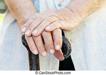 Hands of old senior with walking stick
