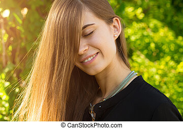 Young woman closing eyes on the background of trees - Young...