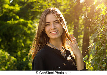 Young woman touching her hair - Young happy woman in black...