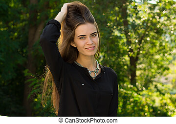 Young woman fixing her hair - Young smiling woman in black...