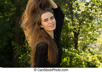 Young woman fixing her hair - Young nice woman in black...