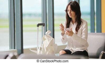 Woman applying lipstick in the airport while waiting her boarding