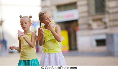 Adorable girls eating ice-cream outdoors at summer. Cute...