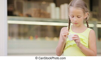 Adorable little girl eating ice-cream outdoors at summer....