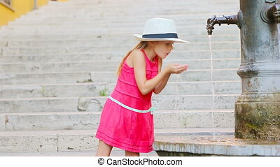 Little adorable girl drinking water from the tap outside at hot summer day in Rome, Italy