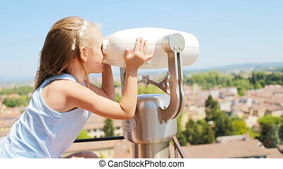Beautiful little girl looking at coin operated binocular on...