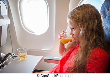 Adorable little girl traveling by an airplane. Kid drinking...
