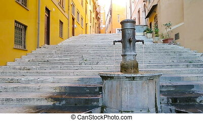 Street fountain in a European city on the street. People quench thirst drinking water outdoors