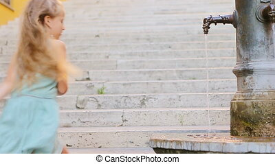 Adorable girl drinking water from street fountain at hot summer day in Rome, Italy