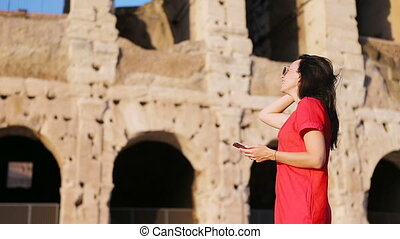 Young woman in front of Colosseum with smart phone in hands...