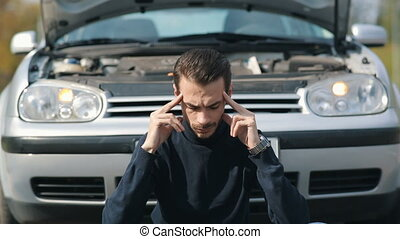 Man with headache in a front of broken car