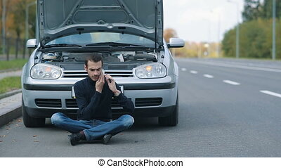 Man sitting in a front of broken with cell phone - Road trip...
