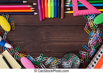 School supplies on a wooden table with space for text, top...