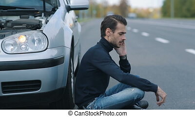 Man siitting near broken car and calling for help - Road...
