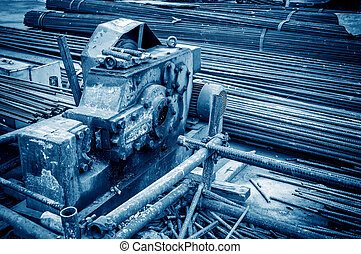 Construction site rebar cutter, blue tone image.