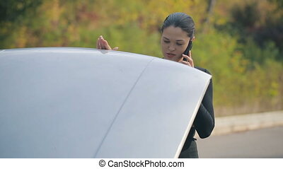 Woman and broken car - Road trip car trouble. A young woman...