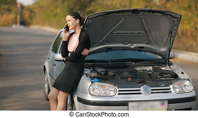 Woman with broken car calling by the phone