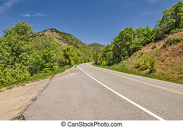 Two Lane Road in the Mountains - Two-lane road with a big...