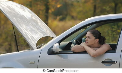 Sad young Woman in broken car - Road trip car trouble. A...