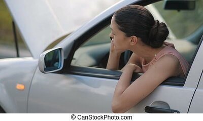 Woman sitting in broken car calling for help