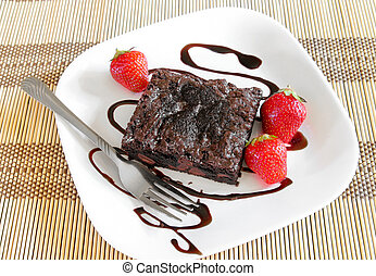 brownie on a white plate with strawberries